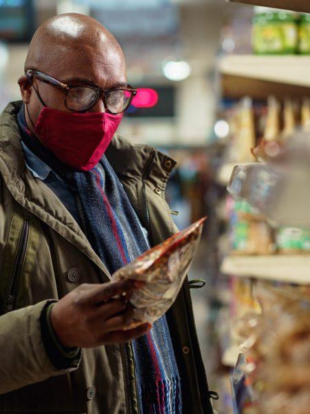 Man wearing red mask choosing crisps in supermarket